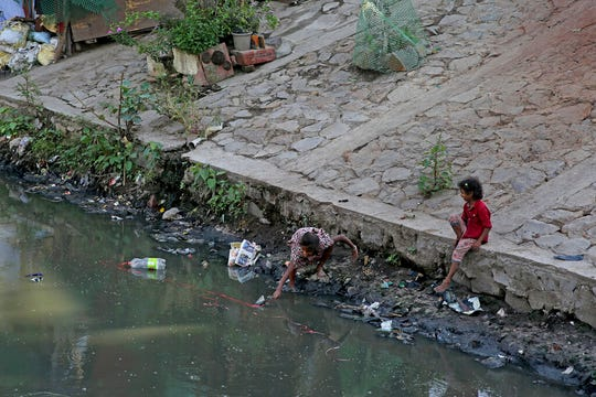 In this Thursday, Sept. 26, 2019 photo, a girl from an impoverished family reaches out to grab a plastic bottle from a canal in New Delhi, India.