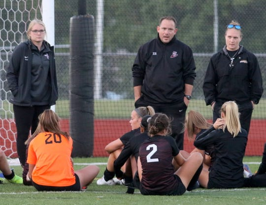 Elmira girls soccer head coach Zach Sarno and assistants Sierra Barr, left, and Amanda Murphy, right, talk to the team after a 2-1 win over Ithaca on Sept. 26, 2019 at Ernie Davis Academy.