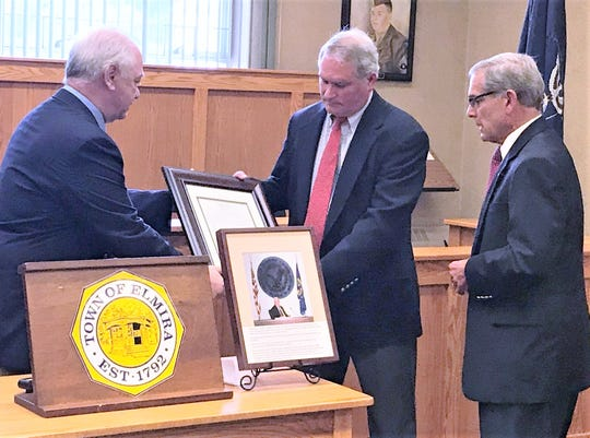 """Elmira Town Supervisor David Sullivan, left, and Town Board member Thomas Milliken, center, present retired Chemung County Executive Tom Santulli with a public service award named in memory of Milliken's father, longtime Chemung County legislator and Chairman Cornelius """"Connie"""" Milliken."""