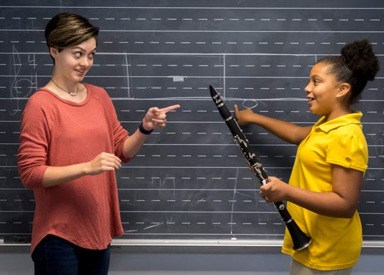 University of Evansville junior Morgan O'Beirne, left, affirms the correct answer from Joshua Academy sixth-grader Noey Cade,11,  during an early morning music program session at Joshua Academy Wednesday morning, Oct. 2, 2019. UE has helped reinstate the music program at Joshua Academy this year which hasn't had the program since 2017.