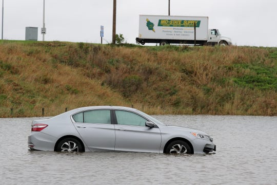 A car left in a parking lot is surrounded by water  Wednesday, Oct. 2, 2019 in a parking lot of Bublitz's Restaurant & Ale House in Lomira, Wis. Storms rolled across the state late Tuesday and early Wednesday prompting the National Weather Service to issue flash flood watches and warnings.