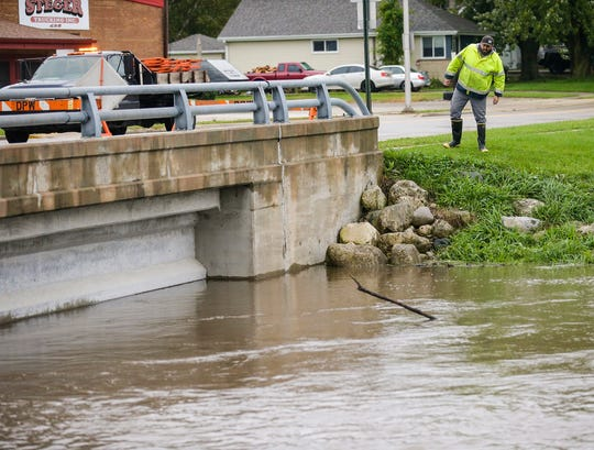 Waupun Department of Public Works' Chuck Stobb monitors the water level on the Rock River Wednesday, Oct. 2, 2019 where it goes under Fond du Lac St. in Waupun, Wis. Fond du Lac St. was closed due to water from the river pushing against the bridge. Heavy rains caused widespread flooding.