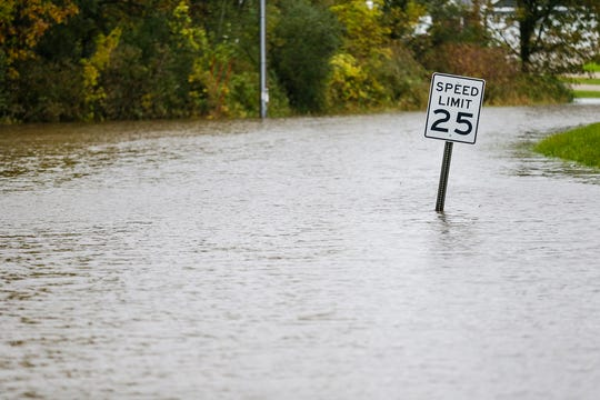 A speed limit sign sticks out of the water Wednesday, Oct. 2, 2019 on River Road in Waupun, Wis. Heavy rains in the area caused widespread flooding in Fond du Lac County.
