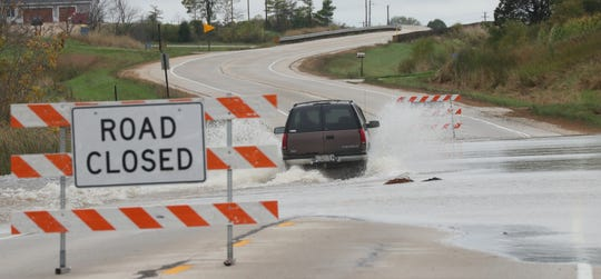 A SUV ignores a road closed sign and drives west on flood-covered Hwy. 28 through the the Theresa marsh Wednesday, Oct. 2, 2019 in Dodge County, Wis. Storms rolled across the state late Tuesday and early Wednesday prompting the National Weather Service to issue flash flood watches and warnings.