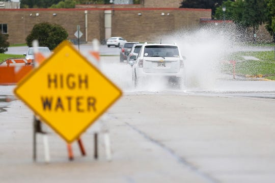 An SUV drives through standing water Wednesday, Oct. 2, 2019 on east Spring Street in Waupun, Wis. Heavy rains caused widespread flooding in the area.