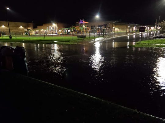 The 300 block of Polk Street is flooded Tuesday night in North Fond du Lac. Resident Julie Miller witnessed a car try to drive through the water and become stuck. Police later blocked off the road.