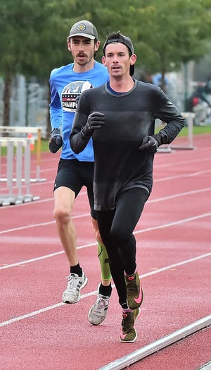 Andrew Epperson, an assistant cross-country and track and field coach at Colorado State, leads Jarrell Mock through an 800-meter run during interval work Tuesday, Oct. 1, 2019, at CSU's Jack Christiansen Track. The workout, on a cold, rainy day, was Epperson's last in Fort Collins before traveling to Doha, Qatar, to compete in the marathon at the IAAF World Championships.