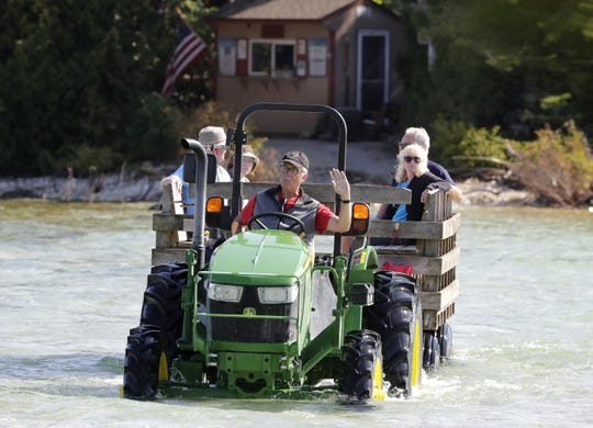 Maritime Museum volunteer Ben Coopman ferries vistors across the Cana Island causeway with a tractor on Tuesday, September 24, 2019, in Baileys Harbor, Wis. High water levels have flooded the causeway. Wm. Glasheen/USA TODAY NETWORK-Wisconsin