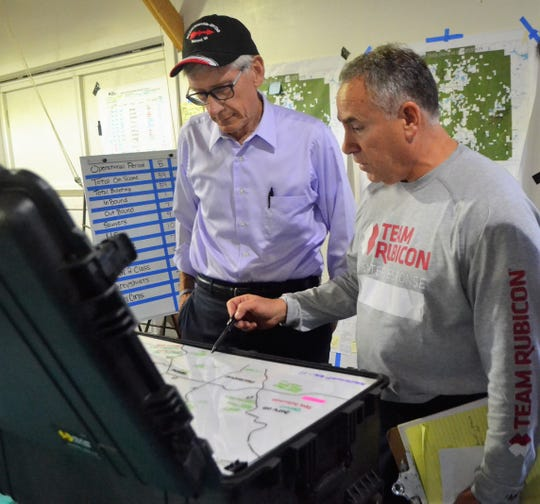 A Team Rubicon member shows Gov. Tony Evers where trails in Oconto County have been cleared and where its members will work on through Sunday.  Evers met with the volunteers from Team Rubicon and Americorps on Tuesday afternoon from their base at the Town of Riverview Community Center and Fire Department.