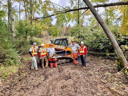 Team Rubicon members poses with an end loader after clearing the same section of trail in northern Oconto County.