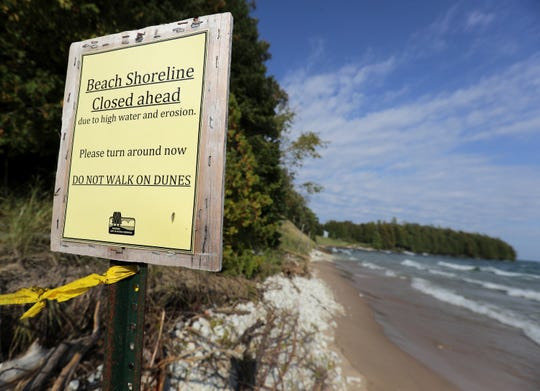 A sign warning visitors Whitefish Dunes State Park beach is closed due to high water and erosion.