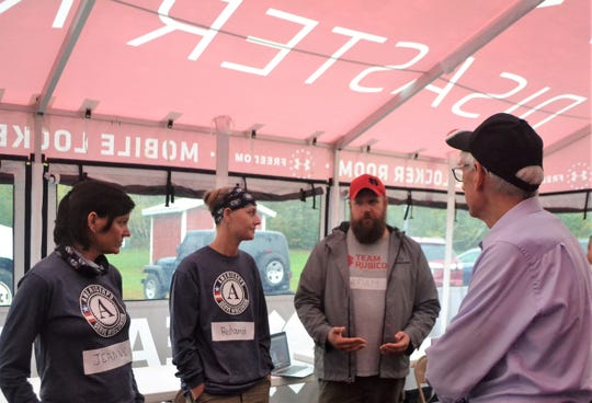 Adam Lemons, a Team Rubicon member from Neenah, talks with Gov. Tony Evers in the town of Riverview on Tuesday. At left are Service Wisconsin officials Jeanne Duffy, excutive director, and program officer Ruhamah Bauman. About 70 young people from Americorps, which Serve Wisconsin oversees, are helping Team Rubicon clear snowmobile trails in northern Oconto County from Sept. 27 to Oct. 6.
