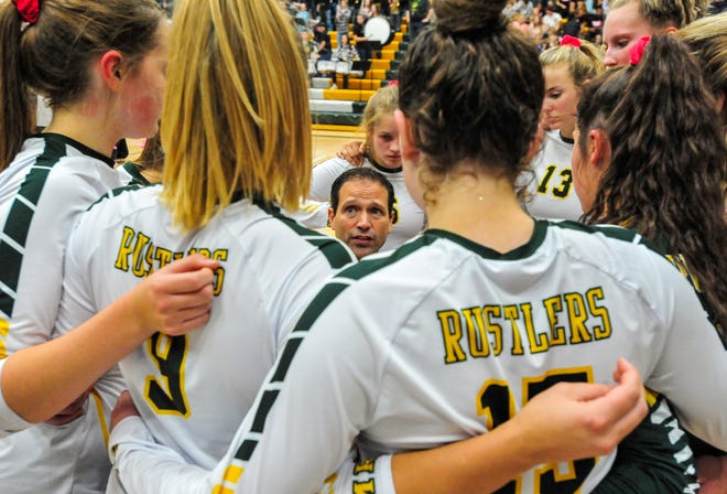 CMR coach Patrick Hiller huddles with his team during a break in the action of last month's crosstown volleyball match against Great Falls High.