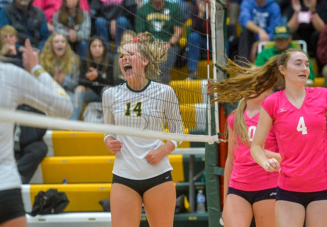 C.M. Russell middle hitter Allie Olsen (14 in white) celebrates a point for her team during the crosstown match against Great Falls High last month.