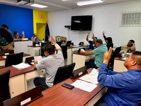Mayors on Oct. 2, 2019 raise their hands to vote on a motion to accept an offer to be on a weekly radio program once again to talk about their village programs. The mayors' council clarified that Yona Mayor Jesse M. Blas remains a mayor, even after his indictment on charges of extortion and bribery and placement in custody.