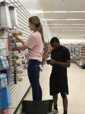 Elizabeth Russell and Kannon Petrie organize items inside the soon-to-be-opened Mighty Dollar store in Gardenside Shopping Center on Zion Road.