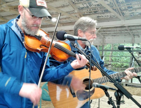 Marc Janssen (left) of Iowa City and Warren Hanlin of West Branch assist with a sound check during Sunday's Fiddler's Picnic at the Johnson County Fairgrounds.  Janssen is president of the Iowa Friends of Old-Time Music.
