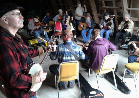 Banjo player J.G. Jensma of Coralville took part in one of the many jam sessions which popped up throughout fairgrounds buildings Sunday in Iowa City.
