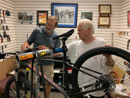 Tom Martin, left, and Jim Ballard, owners of Indian Cycle & Fitness in Ridgeland, study repairs that need to be made to a bike.