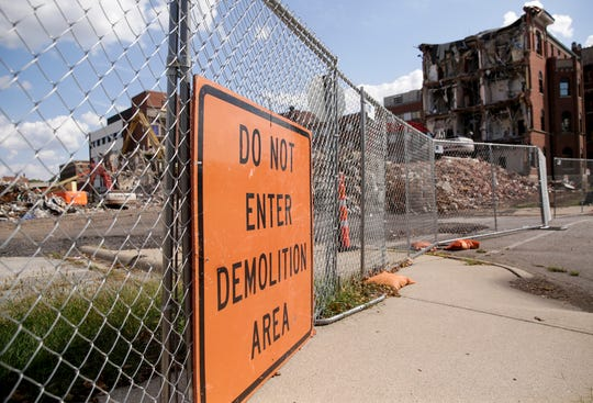 A sign sits on the construction fencing as demotion continues on the Old St. Elizabeth's building on N. 14th Street, Tuesday, Oct. 1, 2019, in Lafayette.
