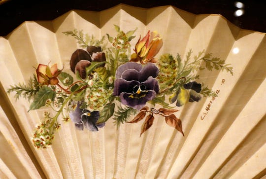 A fan painted with flowers is signed by the artist Caroline Harrison. Harrison, the wife of President Benjamin Harrison, painted the fan in 1890.
