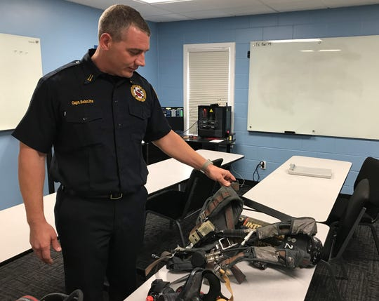 Lancaster Fire Department Capt. Slade Schultz describes the wear and tear on a self-contained breathing apparatus, commonly known as an air pack, the fire department uses. LFD has been awarded a federal grant to help pay for new tanks.