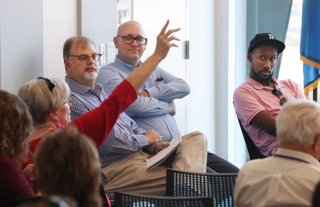 (L-R). Courier Journal reporters Joe Gerth, Joe Sonka and Phillip Bailey look on as a member of the communty raises her hand to make a comment during the Courier Journal's On Kentucky Politics event held at the Northeast Regional branch of the Louisville Free Public Library on Oct. 2, 2019 in Louisville, Ky.