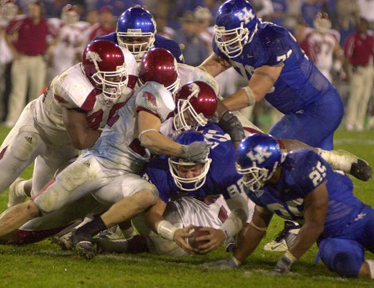 Kentucky quarterback Jared Lorenzen, bottom center, scores from two yards out against Arkansas in the sixth overtime Saturday night, Nov. 1, 2003, in Lexington, Ky. Arkansas' DeCori Birmingham scored on a 25-yard run in a record-tying seventh overtime, and Arkansas stopped Kentucky on a fourth-down play in a 71-63 victory Saturday night.
