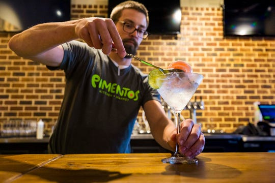 "Bartender Collin Schulke serves the ""Hemingway Went to Paris"" cocktail inside Pimentos in Collierville."