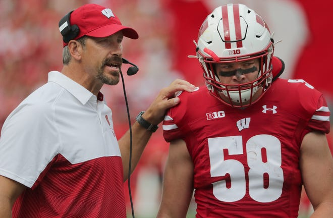 """Wisconsin offensive coordinator Joe Rudolph, shown with linebacker Mike Maskalunas this season, fears varying rules about athlete pay among states will open """"a little bit of a Pandora's box."""""""