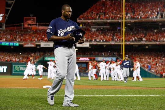 Brewers centerfielder Lorenzo Cain walks off the field as members of the Washington Nationals celebrate their comeback victory in the NL wild-card game.