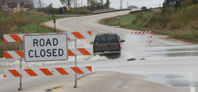 """An SUV ignores a """"road closed"""" sign and drives west on flood-covered Highway 28 through the Theresa marsh in Dodge County on Wednesday. Storms rolled across the state late Tuesday and early Wednesday prompting the National Weather Service to issue flash flood watches and warnings."""