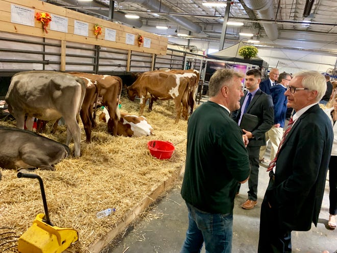 Ben Belzer, center, waits near Gov. Tony Evers, right, while the governor talks to Monticello dairy farmer Bryan Voegeli at the World Dairy Expo in Madison in this October 2019 file photo. Belzer, the governor's personal assistant, died in a tubing accident on Saturday.