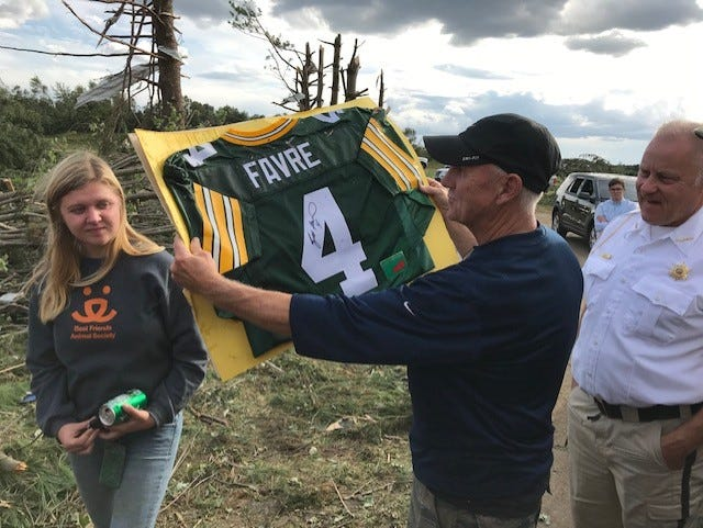 Malcom Gullickson, center, is happy to find his 12-year-old grandson's signed Brett Favre jersey after a tornado destroyed his home in Chippewa County on Sept. 24.