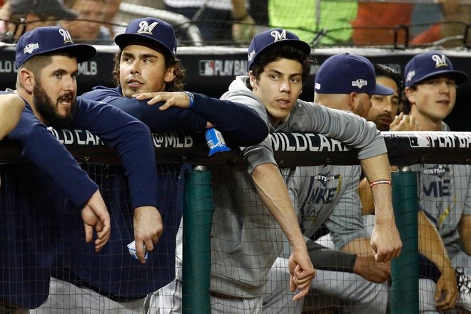 Christian Yelich looks on from the dugout with his teammates Tuesday night.