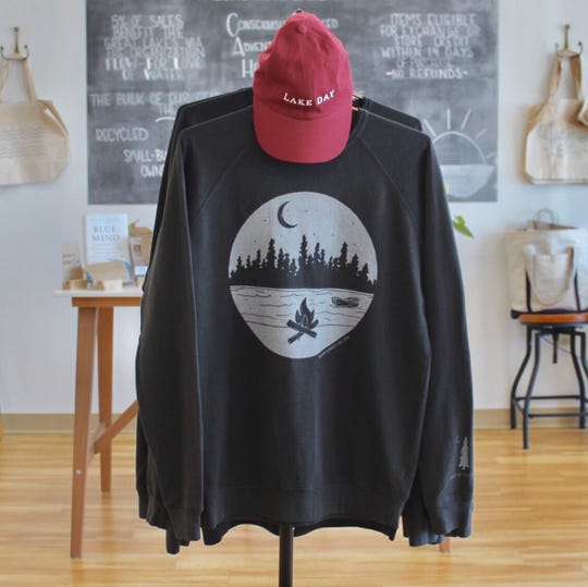 Lake Effect Co. in Pewaukee has started getting in fall and winter apparel, like northerly vibes sweatshirts, which have a lake and tree scene with a campfire and boat.