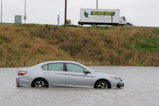A car left in a parking lot is surrounded by water Wednesday, October 2, 2019 in a parking lot of Bublitz's Restaurant & Ale House in Lomira, Wis. Storms rolled across the state late Tuesday and early Wednesday dropping torrential rain across much of the state and likely producing several tornadoes across southern Wisconsin, the National Weather Service said.