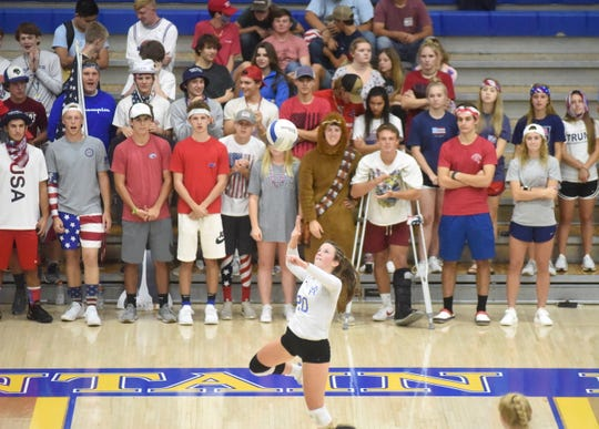 Mountain Home's Elaine Blackmon serves in front of a red, white and blue student section during the Lady Bombers' sweep of Greene County Tech on Tuesday night.