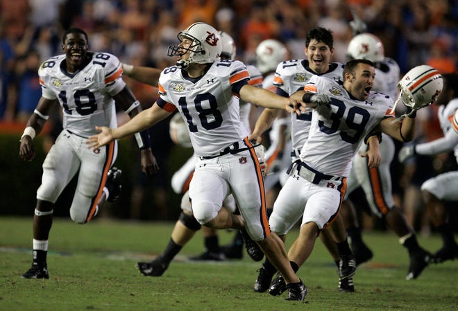 Auburn kicker Wes Byrum, center, celebrates with teammates Kodi Burns (18) and Josh Hebert (39) after Auburn defeated Florida 20-17 on  Sept. 29, 2007, in Gainesville, Fla. Byrum kicked the game-winning field goal.