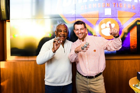 Woody McCorvey and Dabo Swinney show off their trio of national championship rings – one at Alabama, two at Clemson.