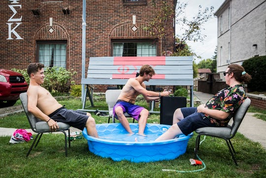 Kaden Tsakrios (from left), John Parks and Alex Tsaparikos cool off with a kiddy pool outside of their fraternity house as temperatures climbed into the 90s Wednesday afternoon.