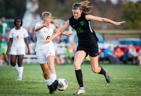 Yorktown's Lea Alexander slips past Delta's Alexus Stone during their game at the Yorktown Sports Park Tuesday, Oct. 1, 2019.