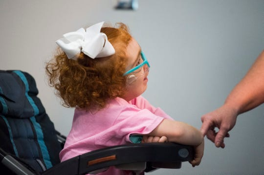 Michelle Gross reaches out to her daughter, Asher, 6, as she speaks at a public hearing about block grant funding for TennCare at the Burlington branch library Oct. 2, 2019.