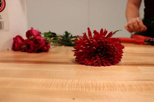 Lauren Bourgeois cuts flower stems to make an autumnal arrangement on Oct. 1, 2019.
