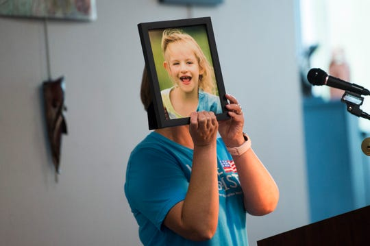 Jessica Fox of Johnson City holds a photo of her daughter at a public hearing about block grant funding for TennCare at the Burlington branch library Wednesday, Oct. 2, 2019. The plan was met with overwhelming opposition at the series of hearings in October.