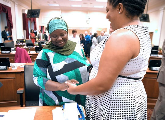 At-Large Council Member Zulfat Suara, left, is greeted by Council Member Delishia Danielle Porterfield before the new council's first meeting at city hall on Tuesday, Oct. 1, 2019.