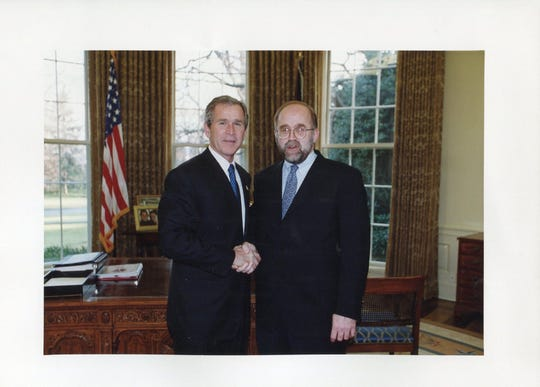 Ron Schlicher, a nearly 30-year employee with the U.S. Department of State, is pictured with President George W. Bush.  Schlicher, who moved to Brentwood after his retirement in 2011, died unexpectedly last month.