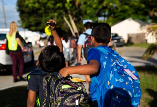 Ever Antonio-Pascual, right, pulls his brother Jesus Antonio-Pascual during a National Walk to School Day event on Wednesday, October 2, 2019, in Bonita Springs. Kids, relatives and teachers from Bonita Springs Elementary School took part in National Walk to School Day to raise attention to pedestrian safety.