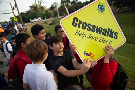 Lorenze Pacheco, a 4th grader in Bonita Springs Elementary School, holds a sign with Erick Ramirez, 9, right, together during a National Walking to School Day event on Wednesday, October 2, 2019, in Bonita Springs.