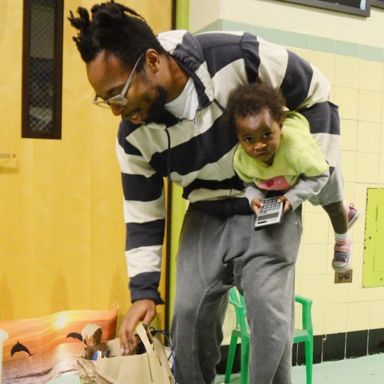 Sefu Fuller and his daughter Hima review their finds at the 2015 Hillside Swap,